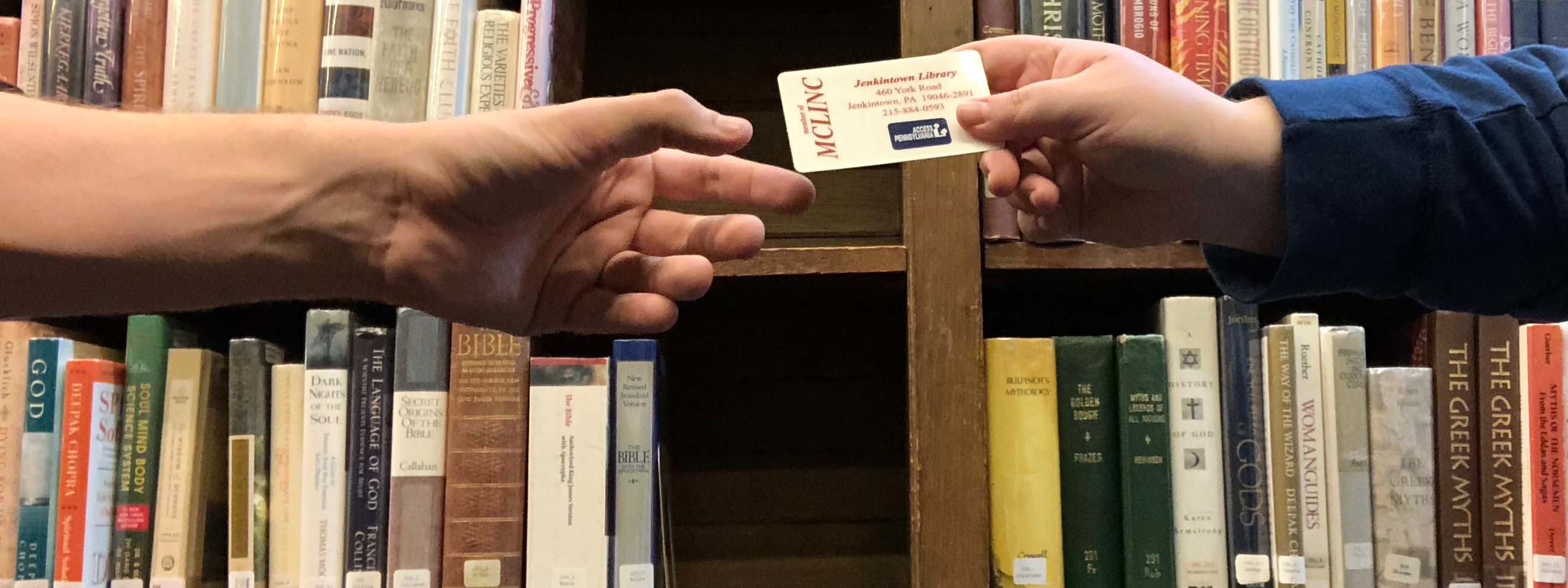 a hand reaching toward a library card being held out