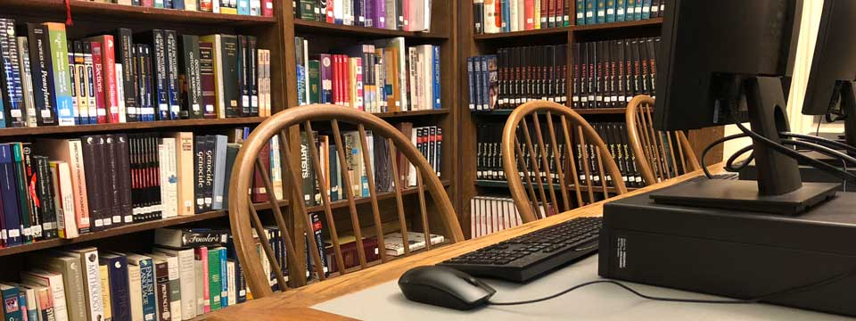 a desk with a computer and mouse, books in background
