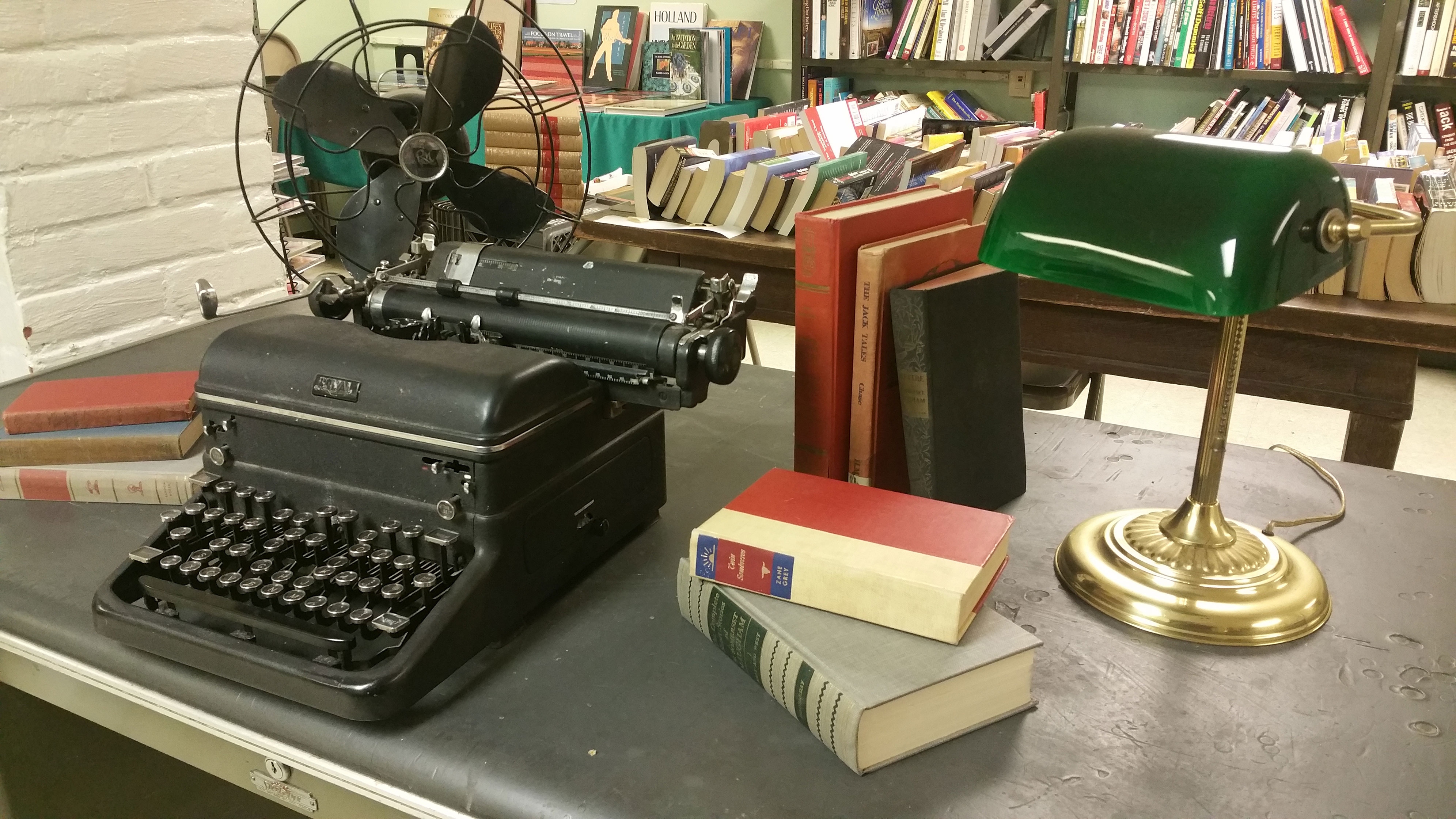 typewriter, lamp, and books on desk