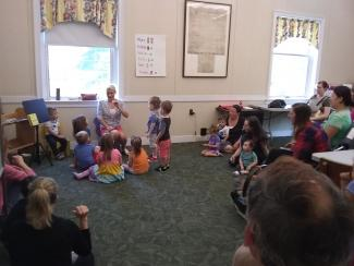 Picture of Katherine Peterson reading a book to a group of children in ASL