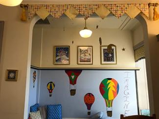 a colorful reading nook with hot air balloons painted on the wall